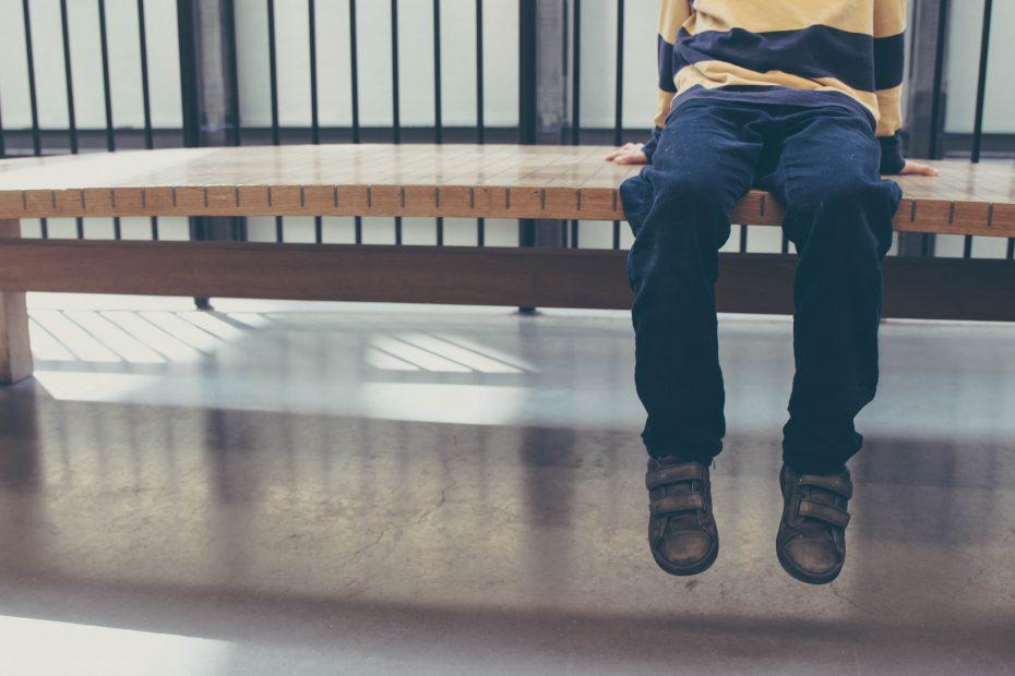 Foto de Michał Parzuchowski en Unsplash donde se observa los pies de un niño sentado en solitario